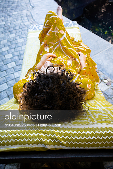 Woman lying on the sun lounger by the pool - p1640m2259935 by Holly & John