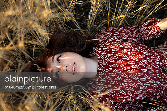 Woman lying in tall grass - p1646m2293212 by Slava Chistyakov