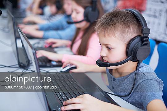Pupils wearing headsets and using laptops in school - p300m1587007 von gpointstudio