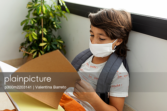 Close-up of boy wearing mask reading book while sitting against wall in school - p300m2203141 by Valentina Barreto