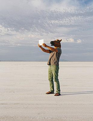 A man wearing a horse mask, taking a photograph with a tablet device, on Bonneville Salt Flats. - p1100m875900f by Paul Edmondson
