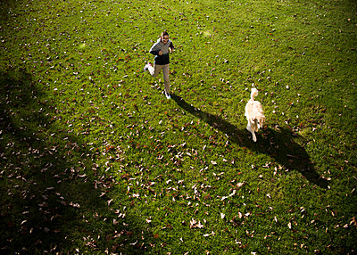 High angle view of teenage boy and Golden Retriever running on grassy field in park during autumn - p1166m2066925 by Cavan Images