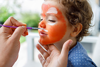 Female painting boy's face through paintbrush at house - p300m2252610 by Ignacio Ferrándiz Roig