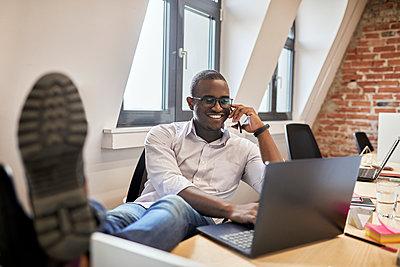 Male entrepreneur talking on smart phone while using laptop at office - p300m2283012 by Zeljko Dangubic