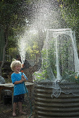 Happy boy spraying water while standing in back yard - p301m1148419 by Tobias Titz