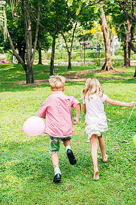Children running with balloon in park - p352m2039892 by Anna Larsson