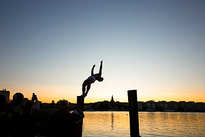 Young man backflipping while friends photographing at lake during sunset - p426m2217835 by Maskot