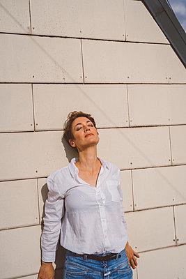 Frau lehnt sich entspannt an Hauswand - p432m2185667 von mia takahara