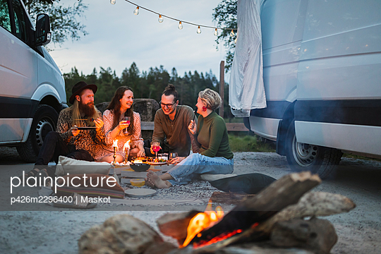 Smiling male and female friends spending leisure time by motor home - p426m2296400 by Maskot