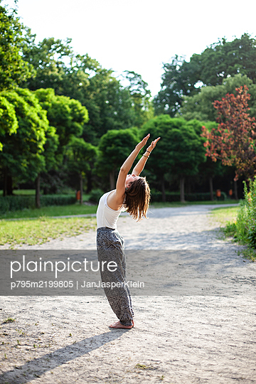 Young woman practicing yoga in park - p795m2199805 by JanJasperKlein