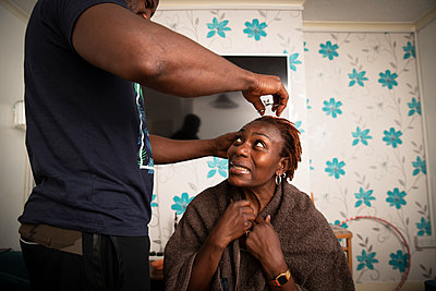 Uncertain woman receiving haircut from husband at home - p1023m2238477 by Himalayan Pics