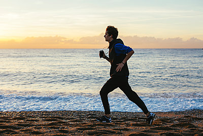 Side view of teenage boy listening music while jogging at beach against sea and cloudy sky - p1166m1508180 by Cavan Images