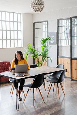 Young businesswoman sitting at desk in loft office using cell phone - p300m2079978 by Giorgio Fochesato