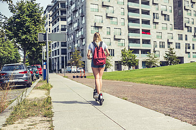 Back view of young woman with backpack riding E-Scooter on pavement, Berlin, Germany - p300m2139685 by Bernd Friedel