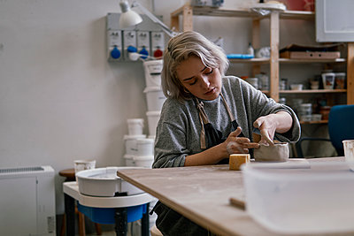 Young woman working on workpiece in pottery - p300m2167166 by Juri Pozzi