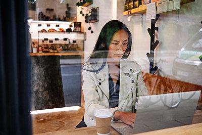 Woman using laptop at coffee shop - p300m2287183 by Angel Santana Garcia