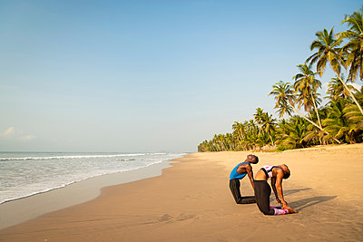 Couple practising yoga on beach - p429m2091827 by Ben Pipe Photography