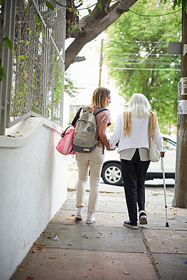 Grandmother and granddaughter holding hands and walking in city - p555m1444221 by Paco Navarro