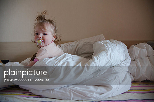 Toddler girl in bed with a pacifier - p1642m2222211 by V-fokuse
