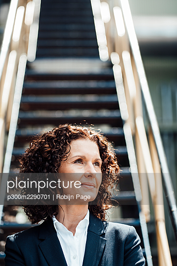 Thoughtful businesswoman looking away in industry - p300m2290701 by Robijn Page