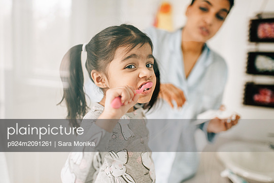 Girl with mother brushing her teeth in bathroom - p924m2091261 by Sara Monika