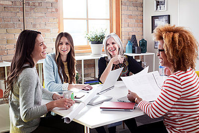 Cheerful businesswomen discussing in board room - p1166m1141465 by Cavan Images