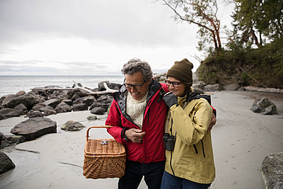 Affectionate active senior couple with picnic basket on rugged beach - p1192m2000435 by Hero Images