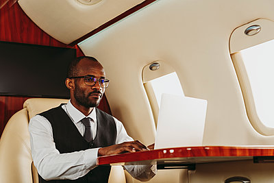 Businessman using laptop while working in private jet - p300m2257041 by OneInchPunch