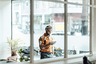 Businessman using mobile phone while standing by office window - p300m2287783 by Gustafsson