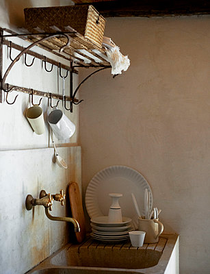Clean crockery and wall mounted rack above sink in Sicilian home - p349m2167768 by Polly Wreford