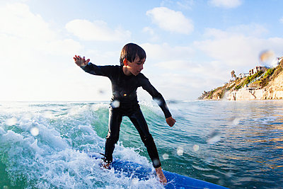 Young boy surfing wave - p429m884147 by Yew! Images