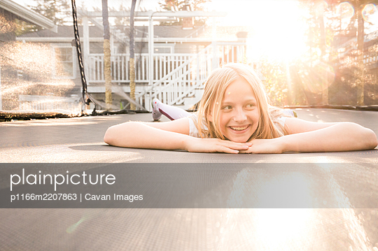 Young Girl Lying on Trampoline on Sunny Evening - p1166m2207863 by Cavan Images