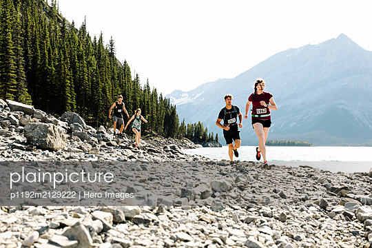 Runners in marathon bibs running along craggy, sunny lakeside - p1192m2129222 by Hero Images