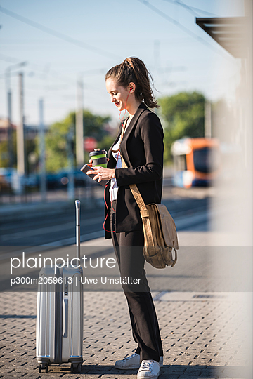 Young woman with luggage at tram station in the city using cell phone - p300m2059613 von Uwe Umstätter