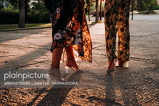 Feet of two elegant women walking outdoors at sunset - p300m2155285 by Jose Luis CARRASCOSA