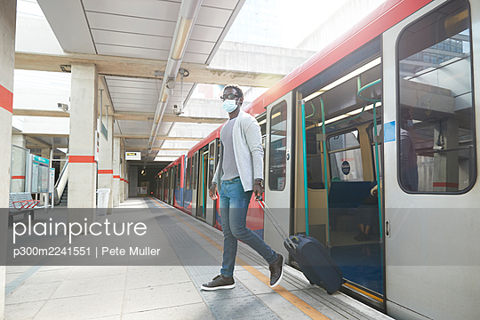 Male entrepreneur business travel disembarking metro train at station during pandemic - p300m2241551 by Pete Muller