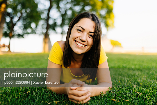 Happy young woman relaxing on grass in park - p300m2293964 by Xavier Lorenzo