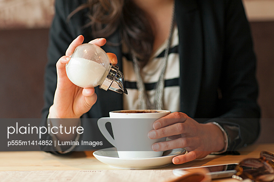 Woman sprinkling sugar in coffee in cafe - p555m1414852 by Lumina Images
