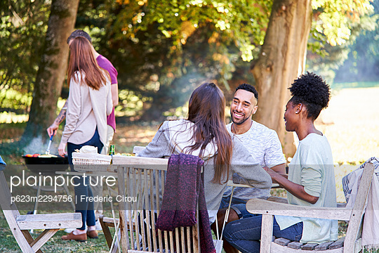Smiling young friends having food at table in garden - p623m2294756 by Frederic Cirou