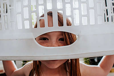 goofy cute child peeking through laundry basket - p1166m2182713 by Cavan Images