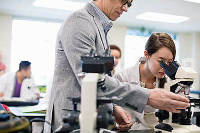 Professor helping female student with microscope in college science lab - p1192m1043649f by Hero Images
