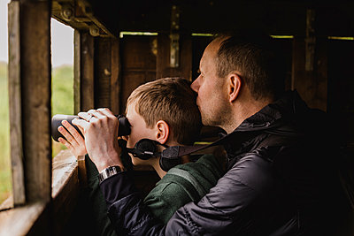 Boy and father birdwatching with binoculars - p300m1449361 by Nicole Matthews