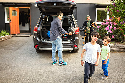 Boys standing while father and mother standing by car outside house - p426m1192980 by Maskot
