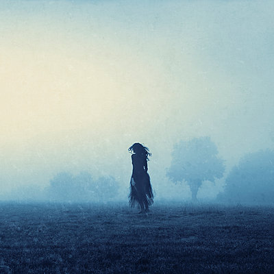 Woman in a misty landscape - p470m2089758 by Ingrid Michel