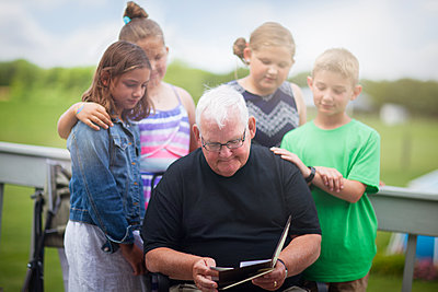 Grandfather surrounded by grandchildren giving him greeting card - p924m1480461 by Rebecca Nelson