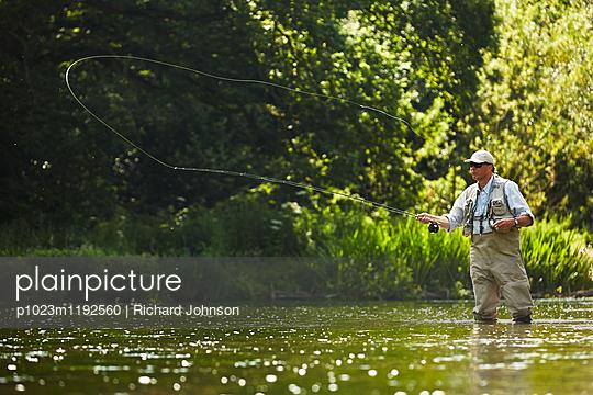 Senior man fly fishing at summer river