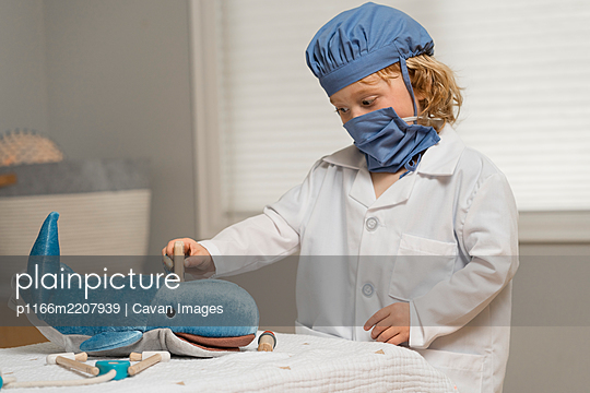 young child wearing medical PPE examines a plush toy whale by taking its temperature with a thermometer - p1166m2207939 by Cavan Images