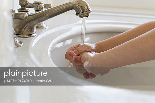 Close-upÊof girl (6-7) washing hands - p1427m2174019 by Jamie Grill