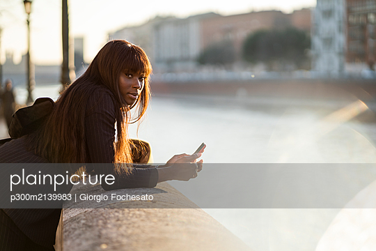 Businesswoman standing with her smartphone at rivershore - p300m2139983 by Giorgio Fochesato