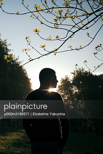 Silhouette of man standing in a park at sunrise - p300m2180571 by Ekaterina Yakunina